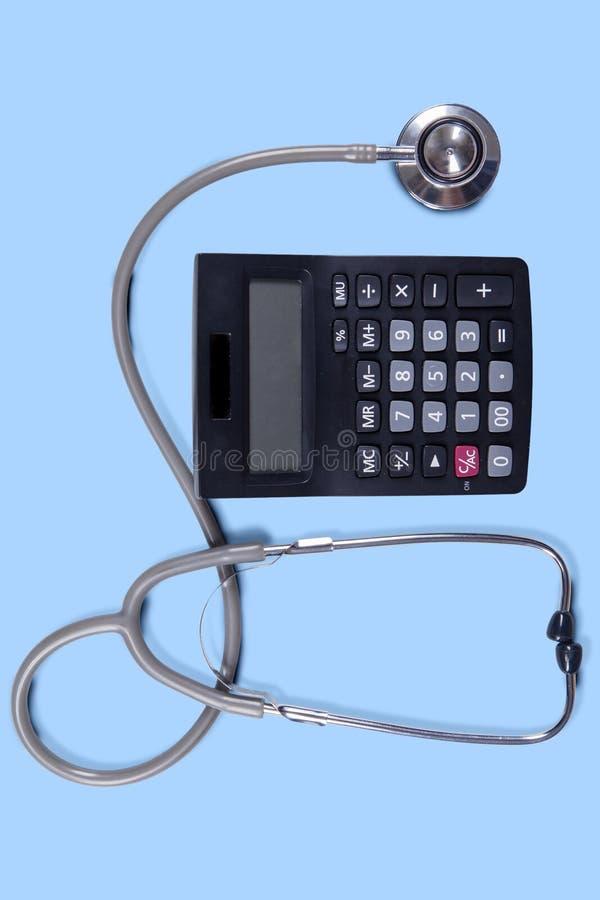 Plan rapproché de stéthoscope avec la calculatrice photographie stock
