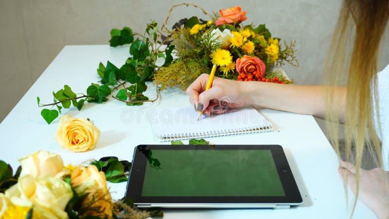Plan rapproché de tir des mains du fleuriste féminin avec le comprimé qui s photos stock