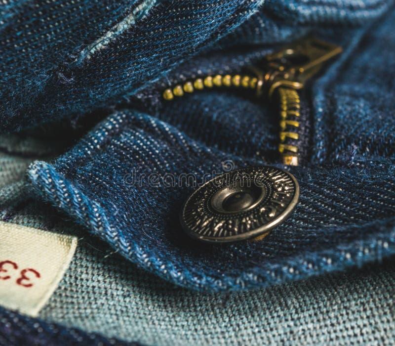 Plan rapproché de tirette de bouton de blues-jean photos stock