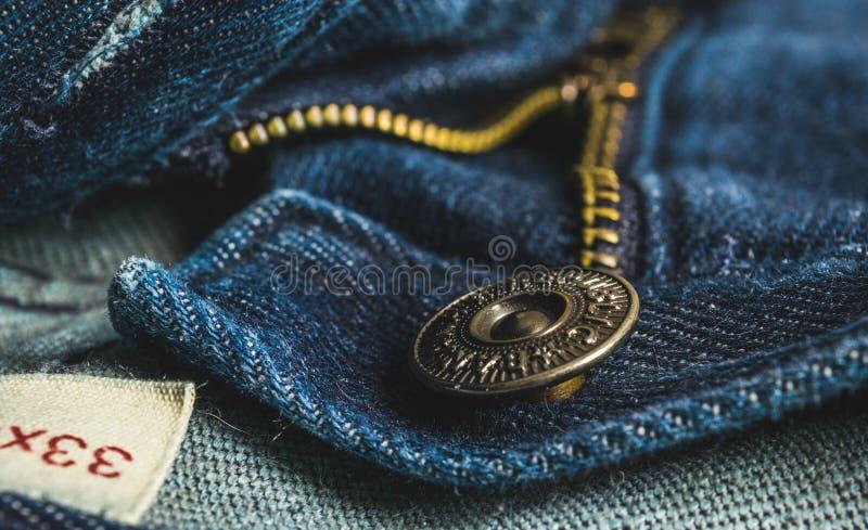 Plan rapproché de tirette de bouton de blues-jean image stock