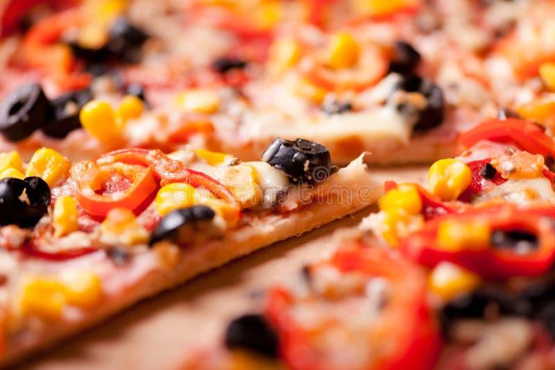 Plan rapproché de tranche de pizza de dîner avec du jambon, olives, mozzarella photographie stock