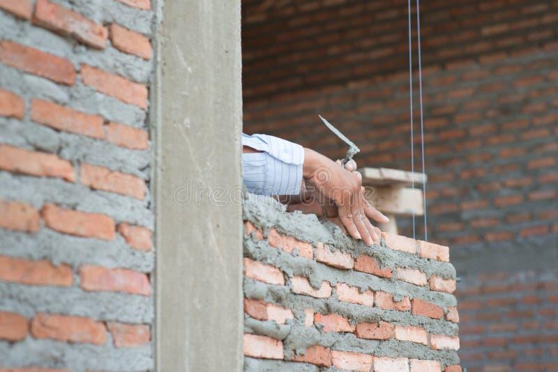 Plan rapproché de travail de maçon de procédé de construction avec l'installation de brique images libres de droits