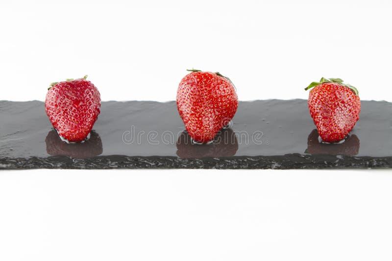 Plan rapproché de trois fraises d'isolement sur une bande rectangulaire d'ardoise humide sur un tir blanc de fond dans la vue cou photos libres de droits
