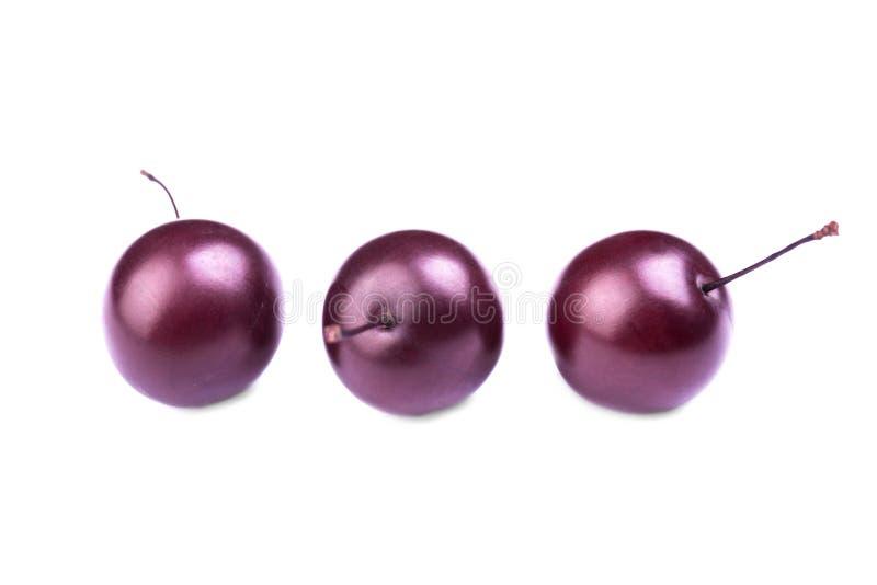 Plan rapproché de trois prunes de cerise rouges, d'isolement sur un fond blanc bonbon à plomb Quelques prunes mûres Passiflore co photographie stock