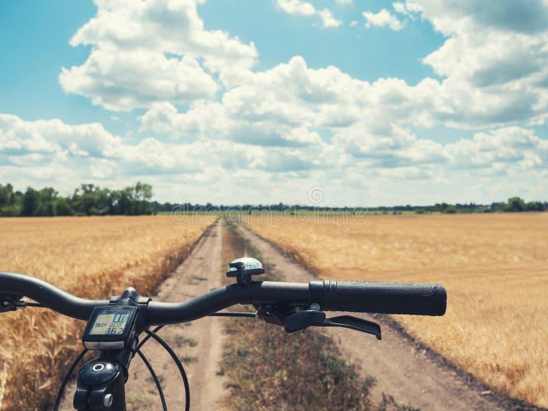 Plan rapproché de vélo de montagne de guidon sur le chemin du champ jaune dans la campagne images stock