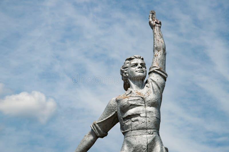 Plan rapproché de vieille statue en pierre délabrée de femme soviétique avec la main en hausse sur le fond de ciel photos stock