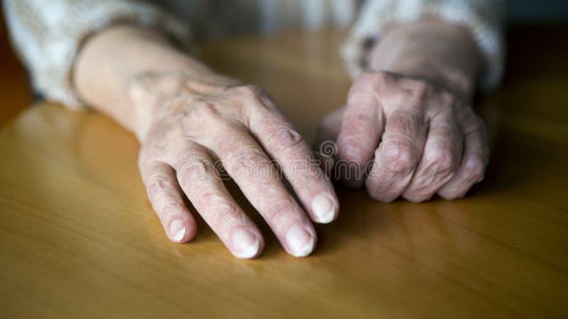 Plan rapproché de vieilles mains femelles sur la table photos libres de droits