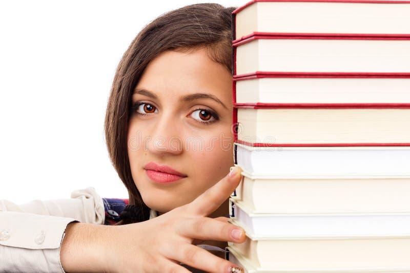 Plan rapproché de visage d'étudiant derrière la pile de livres photos libres de droits