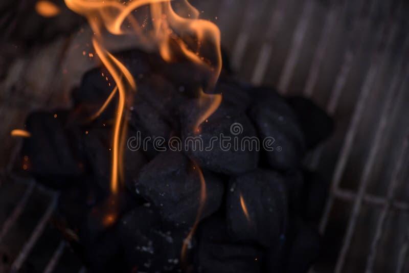 Plan rapproché des briquettes de charbon de bois sur le feu photos stock