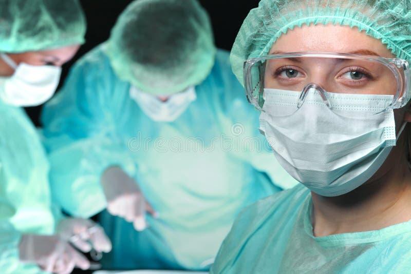 Plan rapproché des chirurgiens effectuant l'opération foyer sur le docteur féminin Concepts d'aide de médecine, de chirurgie et d photos stock