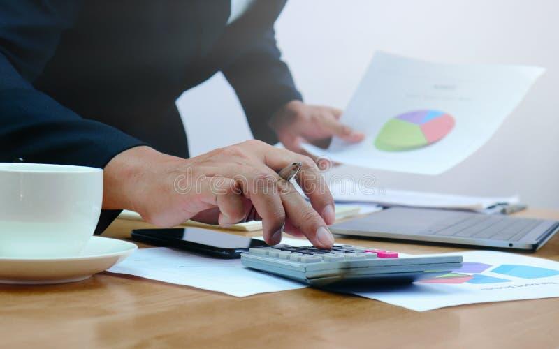 Plan rapproché des comptables masculins qui pressent sur la calculatrice photo stock