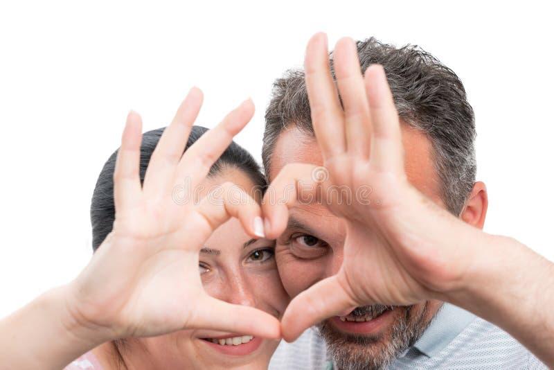 Plan rapproché des couples montrant le symbole de coeur photo libre de droits