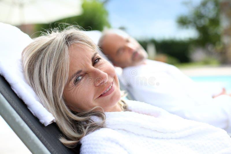 Plan rapproché des couples supérieurs détendant dans de longues chaises photo stock