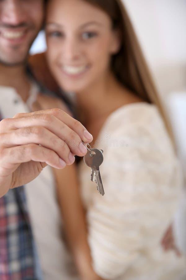 Plan rapproché des couples tenant des clés de nouvel appartement photos stock