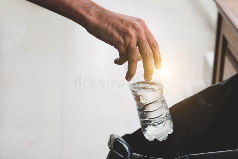Plan rapproché des déchets de lancement de main dans la poubelle noire de sac ?cologie et environnement Pollution et concept réut photographie stock libre de droits