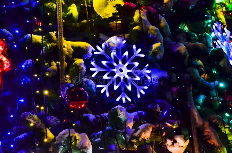 Plan rapproché des décorations rougeoyantes d'arbre de Noël sur un arbre de Noël avec un beau flocon de neige blanc photographie stock libre de droits