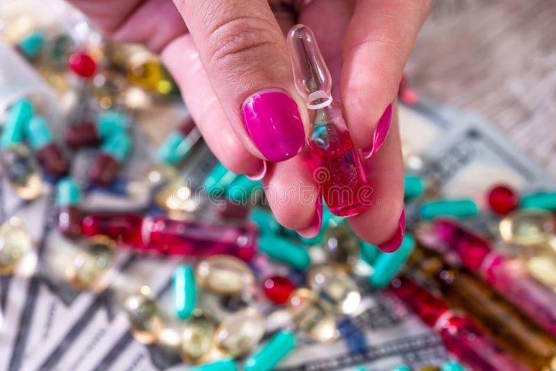 Plan rapproché des doigts femelles avec l'ampoule avec le médicament photo stock
