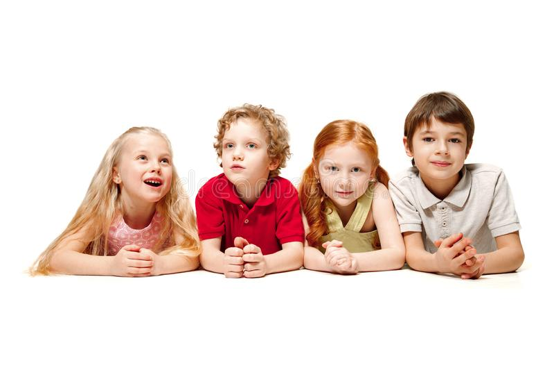 Plan rapproché des enfants heureux se trouvant sur le plancher dans le studio et recherchant, d'isolement sur le fond blanc images libres de droits