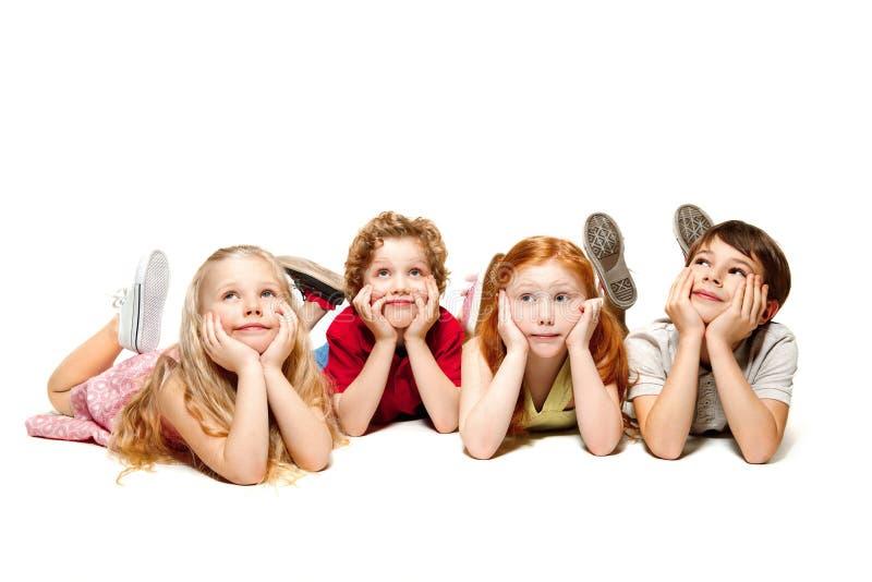 Plan rapproché des enfants heureux se trouvant sur le plancher dans le studio et recherchant, d'isolement sur le fond blanc image libre de droits