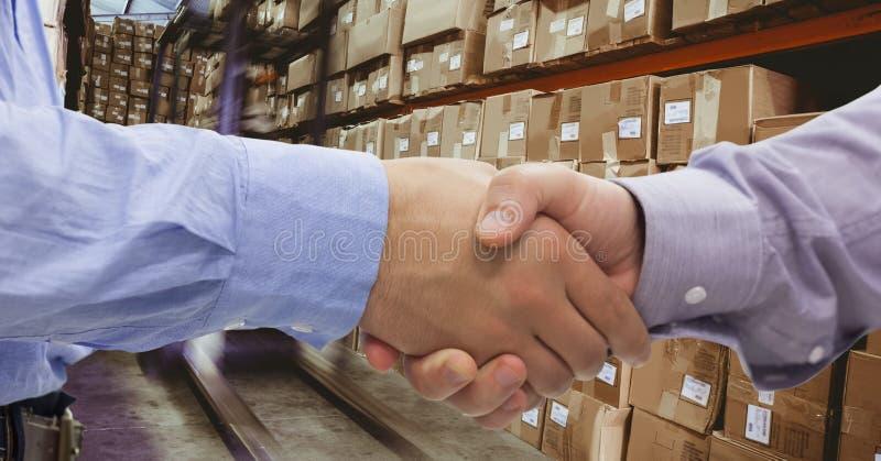 Plan rapproché des gens d'affaires se serrant la main dans l'entrepôt photographie stock libre de droits