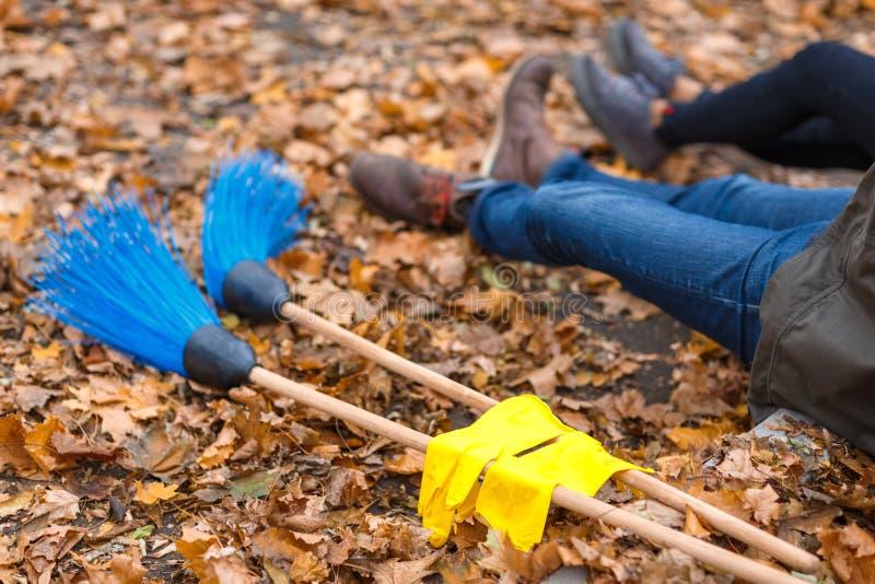 Plan rapproché des jambes d'un homme et d'une fille s'asseyant au sol, à côté des balais du mensonge deux et des gants image stock