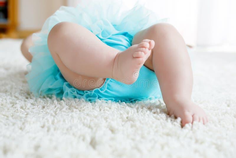 Plan rapproché des jambes et des pieds du bébé sur la jupe de port de tutu de turquoise de fond blanc images stock