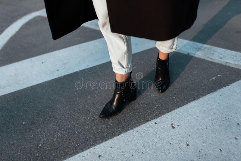 Plan rapproché des jambes femelles dans des jeans de cru dans des chaussures gîtées élégantes en cuir avec un nez aigu La femme é photographie stock libre de droits