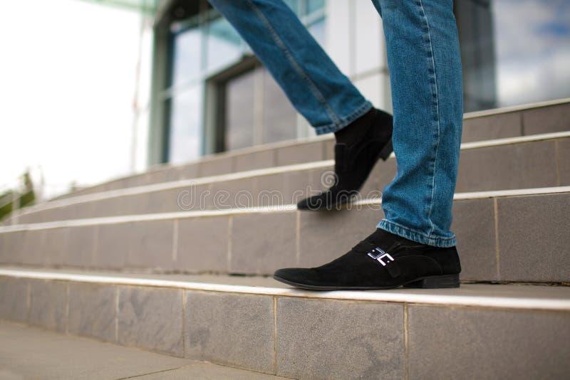 Plan rapproché des jambes masculines sur des escaliers dehors Homme d'affaires marchant vers le bas sur un fond brouillé d'escali photo stock