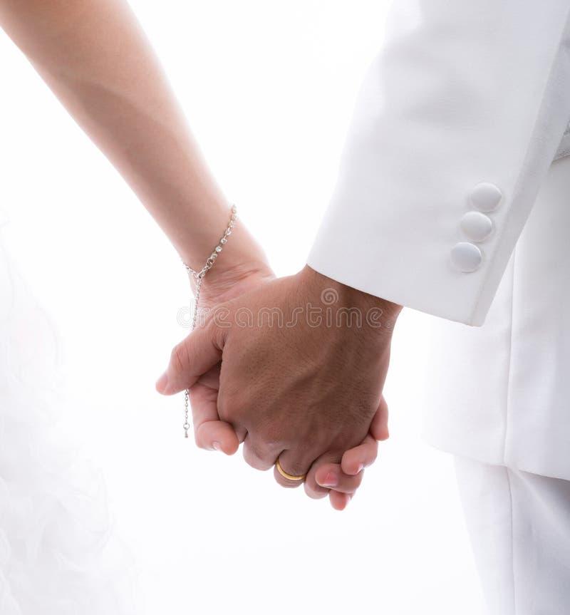 Plan rapproché des jeunes mariés jugeant des mains d'isolement sur le dos de blanc image libre de droits