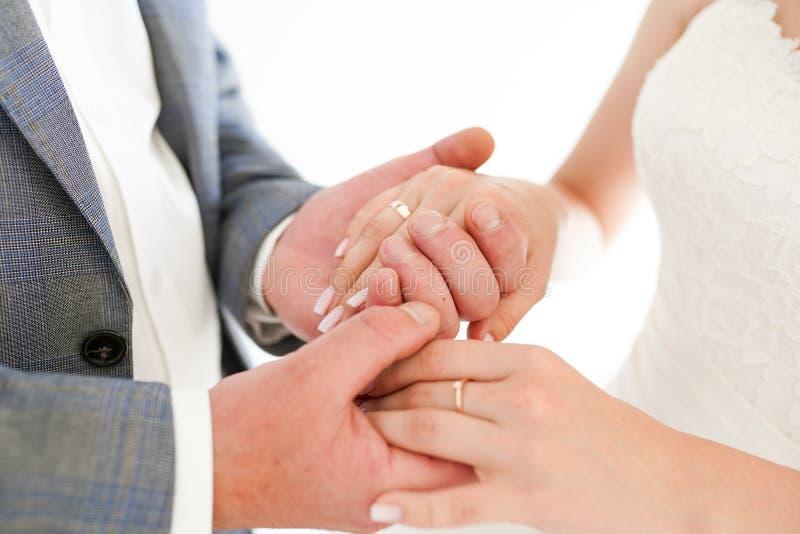 Plan rapproché des jeunes mariés jugeant des mains d'isolement au-dessus d'un fond blanc photos stock
