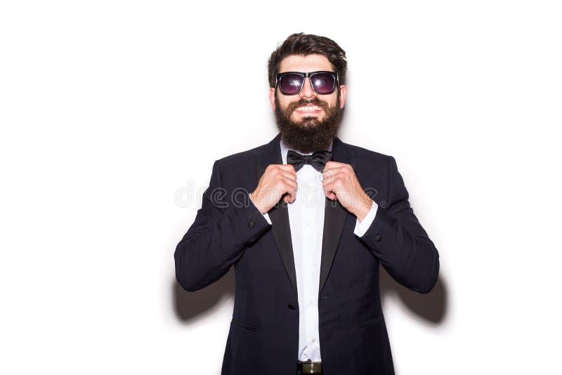 Plan rapproché des lunettes de soleil de port de jeune homme beau ajustant son noeud papillon et regardant l'appareil-photo photo stock
