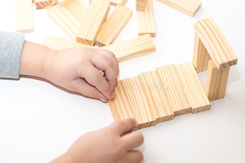 Plan rapproché des mains d'enfants jouant avec les blocs en bois et la maison de construction réserve vieux d'isolement par éduca photos libres de droits