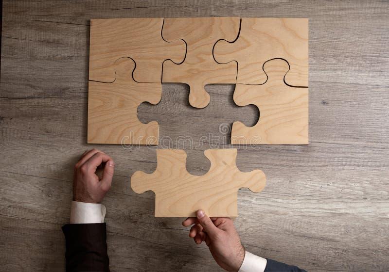 Plan rapproché des mains d'homme d'affaires accomplissant le puzzle denteux image stock