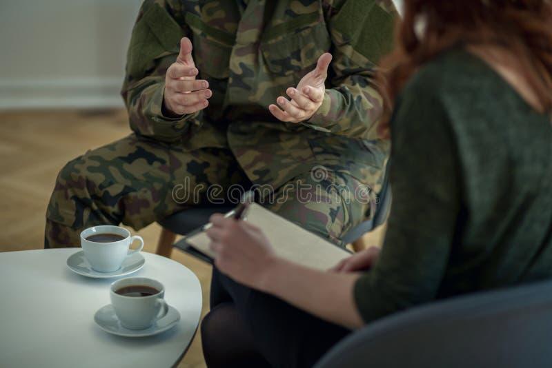 Plan rapproché des mains d'un soldat et de son écriture de thérapeute sur un morceau de papier photos libres de droits