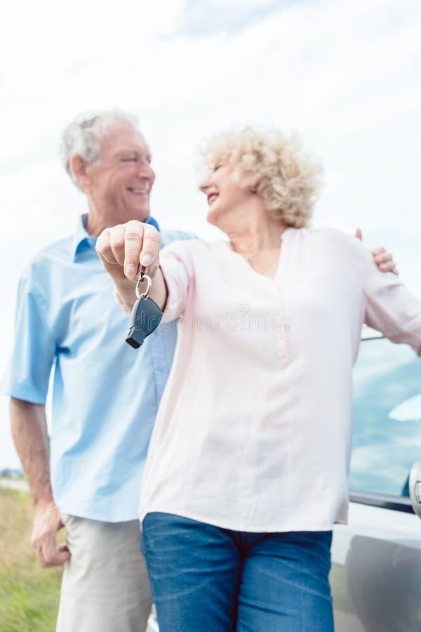 Plan rapproché des mains d'une femme supérieure montrant les clés de sa voiture photo stock
