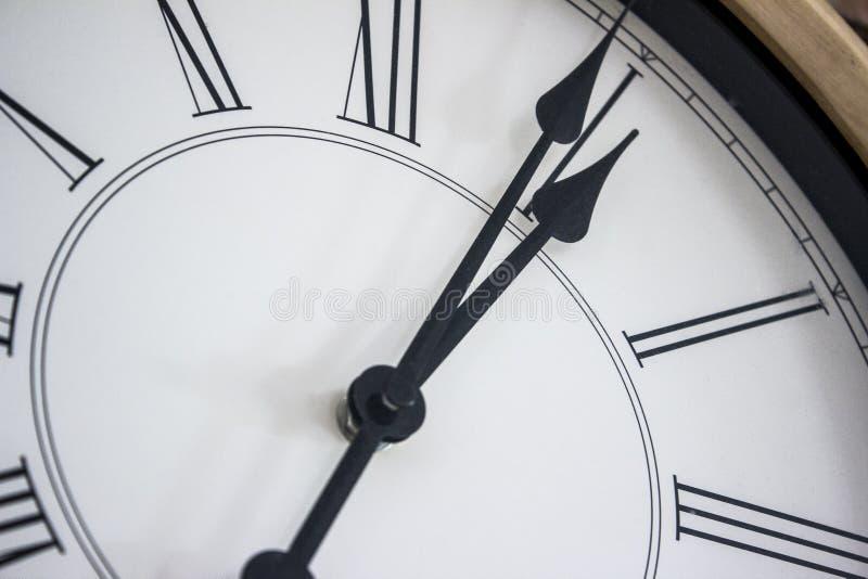 Plan rapproché des mains d'une horloge murale en bois avec les chiffres romains photo libre de droits