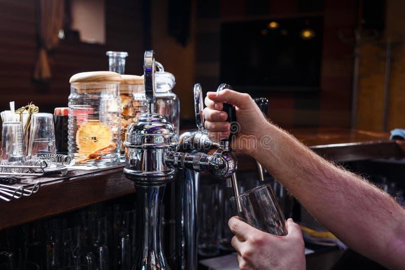 Plan rapproché des mains de barmans versant la bière images stock