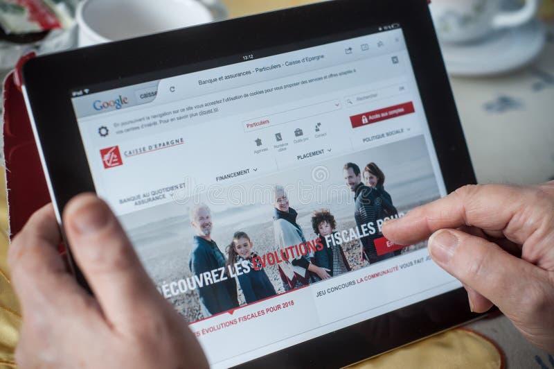 plan rapproché des mains de femme sur la page d'accueil française de banque d'epargne du caisse d du site Web sur le comprimé image stock