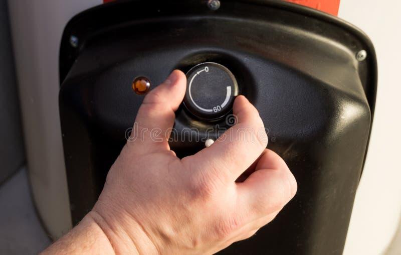 Plan rapproché des mains de l'homme plaçant la température de l'eau dans la chaudière électrique photographie stock libre de droits