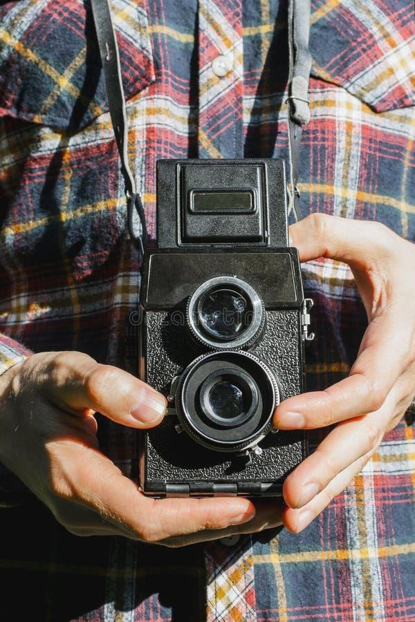 Plan rapproché des mains de l'homme tenant la caméra de film de deux-lentille de cru photo libre de droits