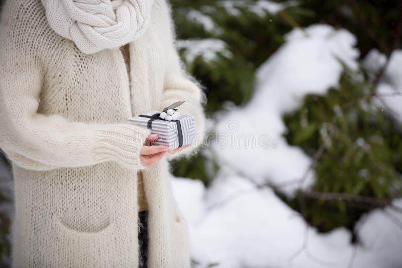 Plan rapproché des mains de la femme tenant un cadeau de Noël gentil outdoors c?l?bration Vacances, concept de cadeaux image libre de droits