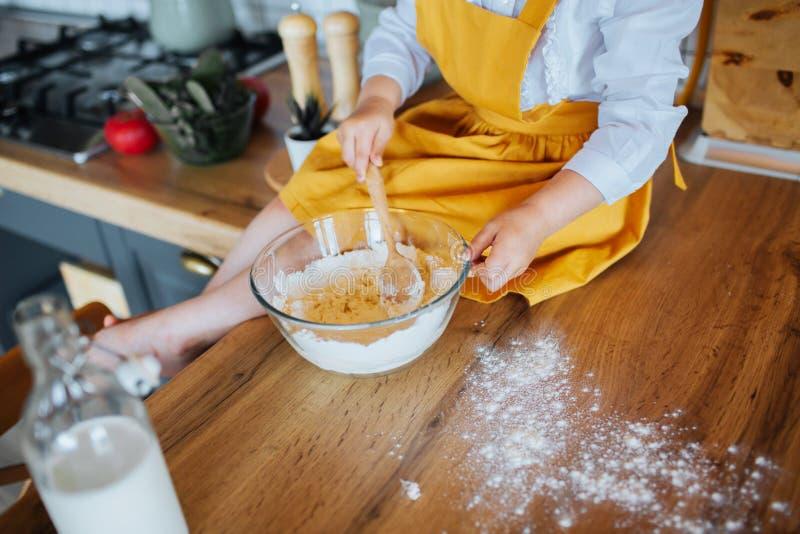 Plan rapproché des mains de la petite fille malaxant la pâte image stock