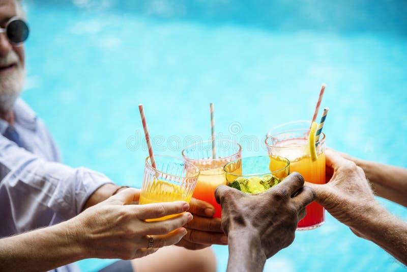 Plan rapproché des mains diverses faisant tinter des boissons ensemble images stock