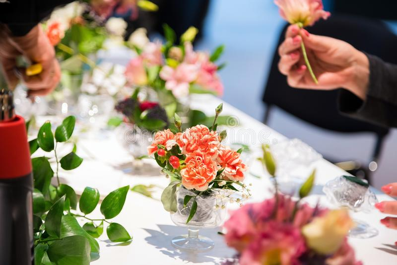 Plan rapproché des mains du fleuriste de jeune femme créant le bouquet des fleurs roses sur la table photos libres de droits