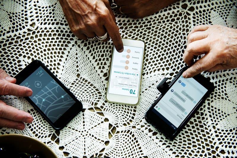 Plan rapproché des mains du ` s de personnes âgées utilisant le téléphone portable image stock