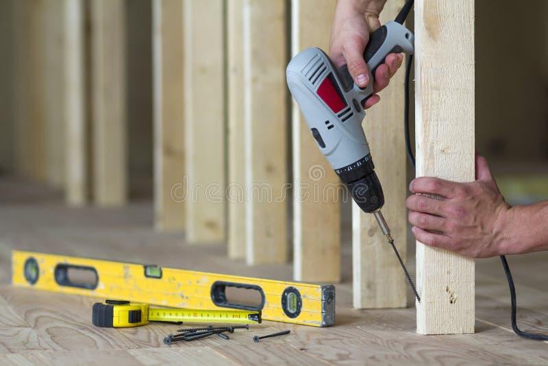 Plan rapproché des mains du ` s de travailleur avec le tournevis sur le fond des outils professionnels et du cadre en bois pour l photos stock