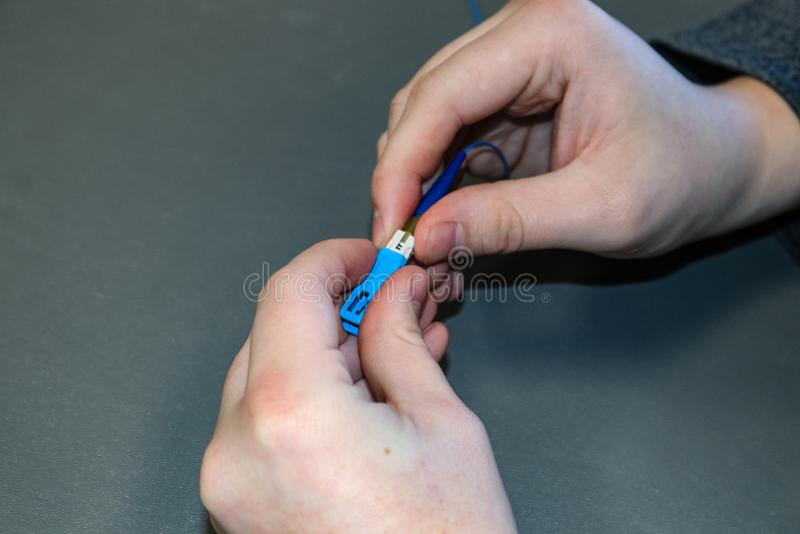 Plan rapproché des mains du technicien de technologie de l'information fonctionnant avec le câblage photographie stock