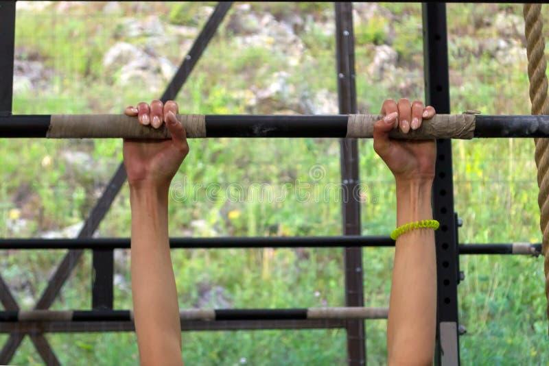Plan rapproché des mains du ` un s de fille avec une manucure sur un fer horizontal image stock