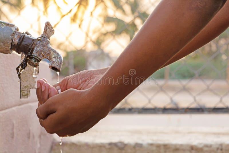 Plan rapproché des mains, eau potable d'enfant directement d'eau du robinet de société en Inde images stock