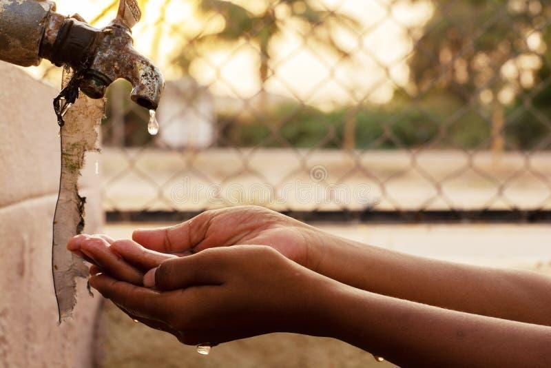 Plan rapproché des mains, eau potable d'enfant directement d'eau du robinet de société en Inde photos libres de droits